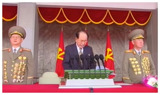 SPA Presidium President and WPK Political Bureau Presidium Member Kim Yong Nam delivers a speech prior to a May 10, 2016 parade celebrating the 7th Party Congress.  Also seen in attendance are WPK Political Bureau Members, Minister of State Security General Kim Won Wong and Chief of the KPA General Staff Vice Marshal Ri Myong Su (Photo: Korean Central TV).