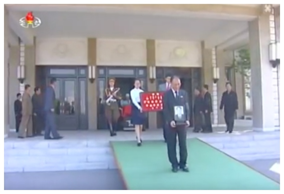 Kang Sok Ju's son carries his official portrait and his granddaughter bears his state awards whilse leaving the funeral parlor at Sojang Center in Pyongyang on May 22, 2016 (Photo: Korean Central TV).