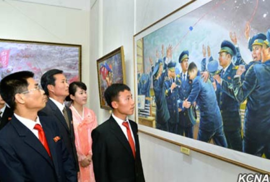DPRK citizens look at a painting depicting National Aerospace Development Agency personnel celebrating a rocket launch (Photo: KCNA).