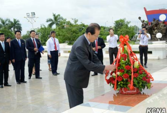 WPK Vice Chairman and WPK Political Bureau Member Choe Tae Bok arrange a ribbon on a floral basket during a visit to the Kaysone Phomvihane memorial in Vientiane, Laos on June 8, 2016 (Photo: KCNA).