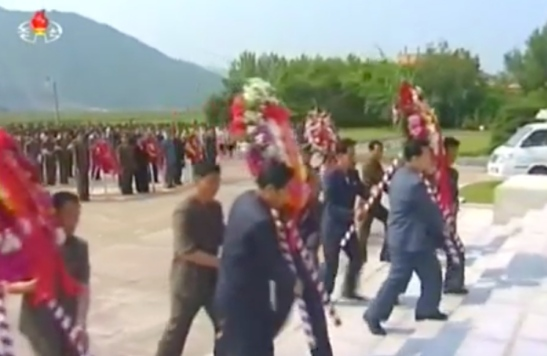 Floral wreaths are delivered to the foot of a Kim Hyong Jik statue in Chunggang County, Chagang Province on June 5, 2016 (Photo: Korean Central TV).