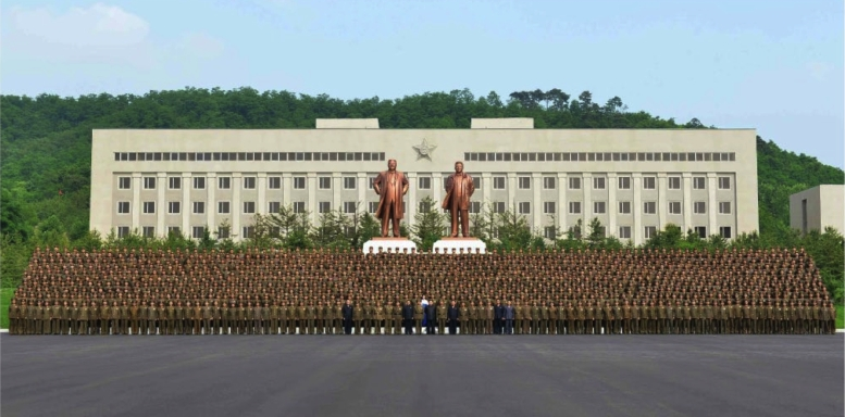 Commemorative photograph of Kim Jong and senior WPK Munitions Industry Department officials with the administration and faculty of the National Defense Industry (Photo: Rodong Sinmun).