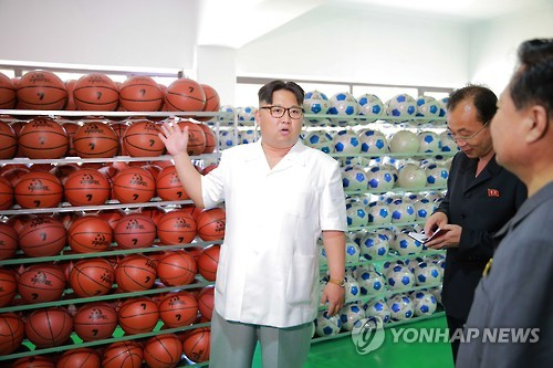 Kim Jong Un discusses products of the Pyongyang Sports Apparatus Factory (Photo: KCNA-Yonhap).