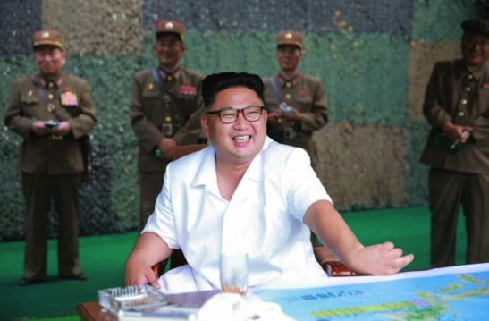 Kim Jong Un smiles during a ballistic missile drill in a photo that appeared on cover of the July 20, 2016 edition of the WPK daily newspaper Rodong Sinmun.  The man standing on the right appears to be WPK Munitions Industry Department Deputy Director Kim Jong Sik (Photo: Rodong Sinmun).