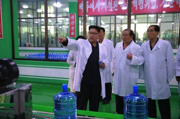 Kim Jong Un tours a bottling section at the Ryongaksan Spring Water Factory in Pyongyang in a photo which appeared top-center on the front page of the September 30, 2016 edition of the WPK daily organ Rodong Sinmun (Photo: Rodong Sinmun).