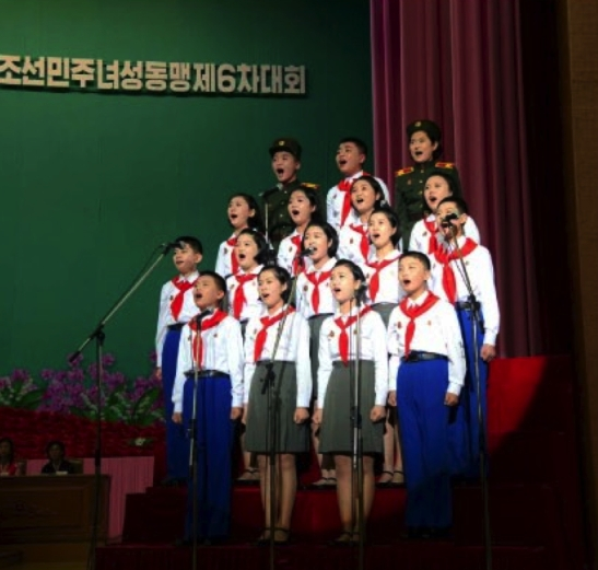 Representatives of the Korean Children's Union make a congratulatory presentation during the Women's Union's 6th Congress in a photo which appeared top-center of page 7 of the November 19, 2016 edition of the WPK daily organ Rodong Sinmun (Photo: Rodong Sinmun).