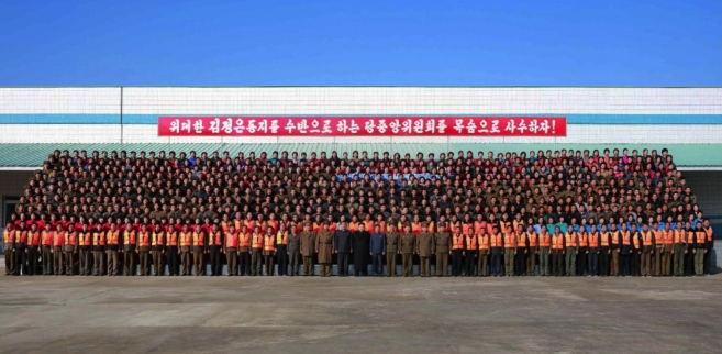 Commemorative photograph of Kim Jong Un with officials and employees of the August 25 Fishery Station in photos which appeared on the bottom of page 2 of the November 20, 2016 edition of the WPK daily newspaper Rodong Sinmun (Photo: Rodong Sinmun).