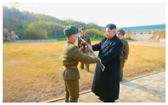 Kim Jong Un presents an automatic rifle to a service member of the Changjae Islet coastal defense detachment. Behind Jong Un are a member of the Guard Command and the head of close security escort detail (Photo: Korean Central Television).