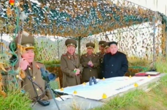Director of the KPA Artillery Bureau Colonel-General Pak Cho'ng-cho'n (left on the telephone) calls in orders during the artillery exercise (Photo: Korean Central Television).