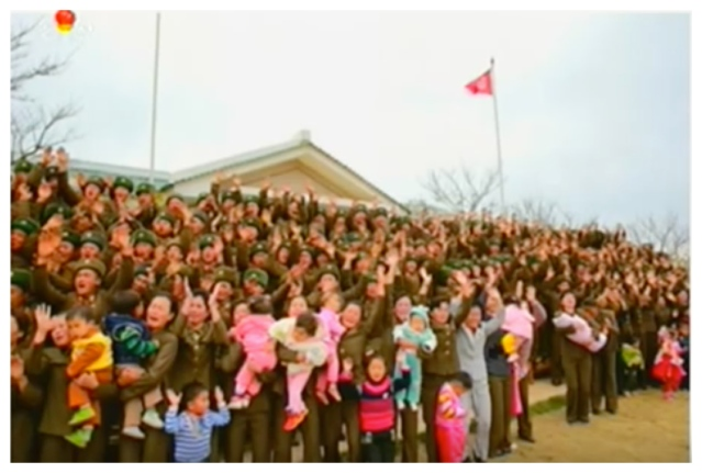 Family members of KPA service members and officers deployed to Mahap Islet greet Kim Jong Un prior to a commemorative photo-op (Photo: Korean Central Television).