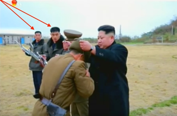 Kim Jong Un presents a pair of binoculars to a member of the islet defense detachment. Annotated are two members of Jong Un's bodyguard unit participating in the ceremony (Photo: Korean Central Television).