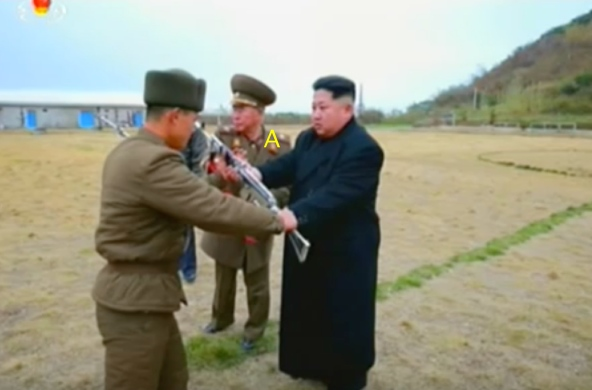 Kim Jong Un presents a machine gun to a member of the island defense detachment. Also seen participating in the ceremony is Chief of the KPA General Staff VMAR Ri Myo'ng-su [A] (Photo: Korean Central Television).