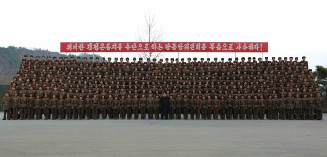 Kim Jong Un poses for a commemorative photo with participants in the MLRS contest which appeared on the top center of page 2 of the November 19, 2016 edition of the WPK daily organ Rodong Sinmun (Photo: Rodong Sinmun).