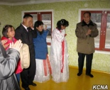 WPK Vice Chairman for Planning and Finance Kwak Pom Gi (right) applauds whilst attending a house warming in North Hamgyo'ng Province (Photo: KCNA).