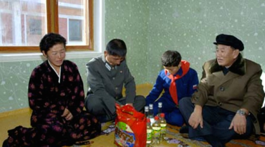 WPK Vice Chairman for Intelligence and South Korean Affairs Kim Yong Chol (right) meets with the family of a Ministry of Railways employee after they moved into their new apartment in North Hamgyo'ng Province (Photo: Korean Central News Agency).