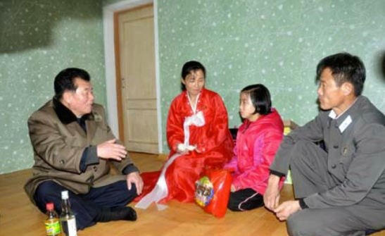 WPK Vice Chairman for Economic Affairs O Su Yong (left) talks with a girl whilst attending a house warming in North Hamgyo'ng Province (Photo: KCNA)
