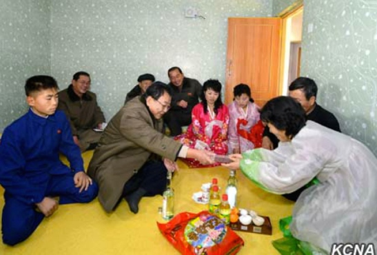 WPK Vice Chairman for Munitions Industry Ri Man Gon presents a gift whilst attending a house warming in North Hamgyo'ng Province (Photo: KCNA).