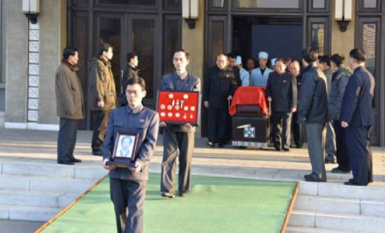 Departing for the cemetery, members of Ryu Mi-yo'ng's family carry her portrait and her state awards in front of her casket at the Sojang Center in Pot'onggang-kuyo'k in Pyongyang (Photo: KCNA).