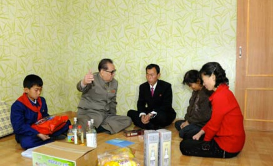 WPK Vice Chairman for International Affairs Ri Su Yong (2nd L) talks with a family whilst attending a house warming (Photo: KCNA).