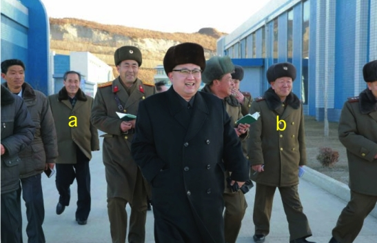 Kim Jong Un tours the Ku'msanp'o Fishery Station in a photo which appeared on top-center on page two (2) of the January 15, 2016 edition of the WPK daily organ Rodong Sinmun.  Tagged in attendance are WPK Central Committee Department Director Kim Yo'ng-su [a] and KPA General Political Department Director VMAR Hwang Pyo'ng-so' [b] (Photo: Rodong Sinmun/KCNA).