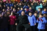 Kim Jong Un smiles whilst posing for a commemorative photograph with students and teaching staff of the Pyongyang Orphans' School in a photo which appeared top center on the front page of the February 2, 2017 edition of the WPK daily organ Rodong Sinmun (Photo: Rodong Sinmun).